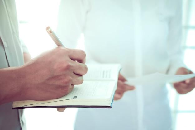 Женщины врач и мужчины доктор, пишущий блокнот, обсуждая информацию о профиле пациента в больнице. Premium Фотографии