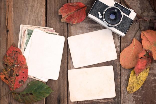 レトロカメラと空の古いインスタント紙フォトアルバムは、秋の境界線のデザインでは、秋の季節の思い出と懐かしさの概念 - の葉の木製のテーブルで木製のテーブル。ヴィンテージの素朴なスタイル。 Premium写真