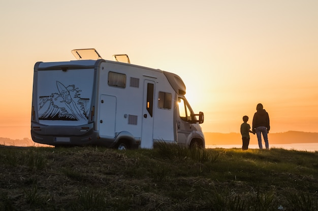 Мать и сын, наблюдая закат с их дом на колесах на берегу моря Premium Фотографии