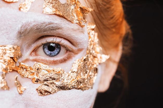 青い目のクローズアップ。金箔を使った珍しいメイクの女の子。匿名。仮装ハロウィーン Premium写真