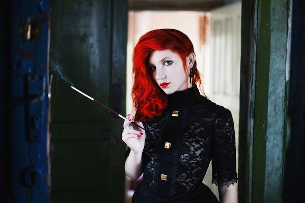 Рыжая девушка с красными губами в темной комнате, женщина держит мундштук с сигаретой в руке Premium Фотографии