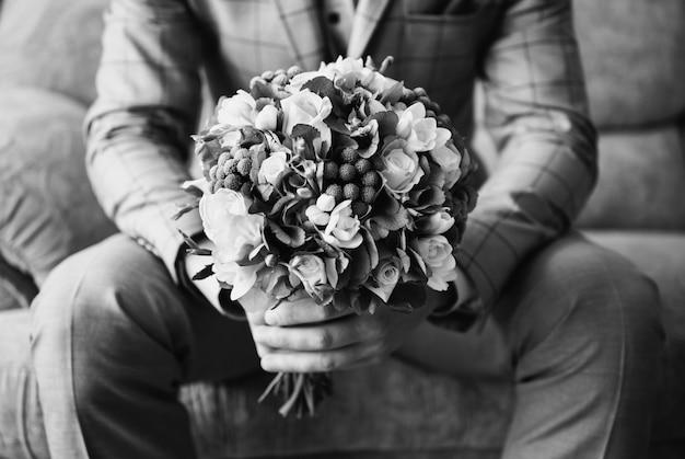 黒と白のアート写真モノクロ、花束を持ってスーツを着た新郎。ウェディングブートニア Premium写真