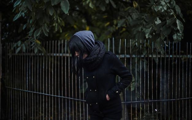 Одинокая девушка в черном пальто, брюнетка, депрессия, одиночество Premium Фотографии