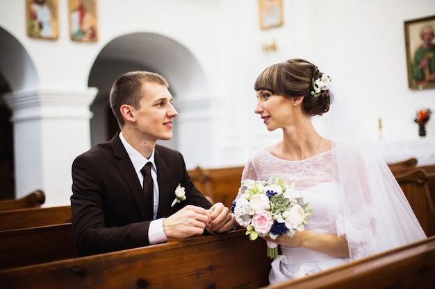 教会で白いドレスを着た新郎新婦。結婚式。幸せな家族 Premium写真