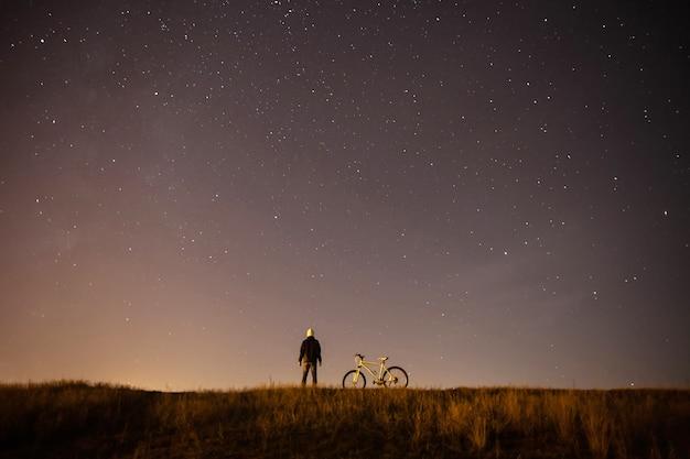 Звездное небо, ночь, астрофотография, силуэт человека, человека, стоящего рядом с горным велосипедом на звездном небе, белого велосипеда Premium Фотографии