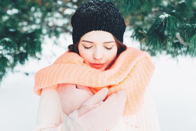 ピンクのニットスヌードを着ている若いブルネットの女性の冬の肖像。目を閉じて女の子。 Premium写真