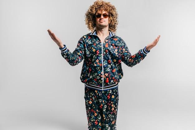 白い背景の上に離れて手で膝の上に立っている巻き毛を持つスタイリッシュな男。 Premium写真