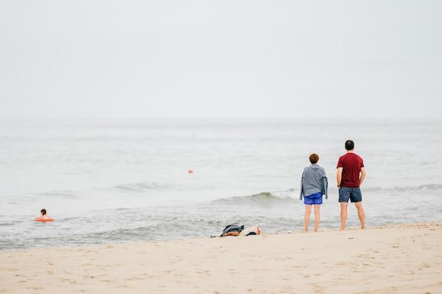 Взгляд от задней части мужчины и женщины смотря на море Premium Фотографии