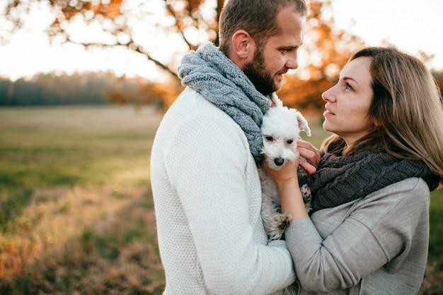 夏の日没のフィールドでハグ面白いペットとロマンチックなカップル。 Premium写真