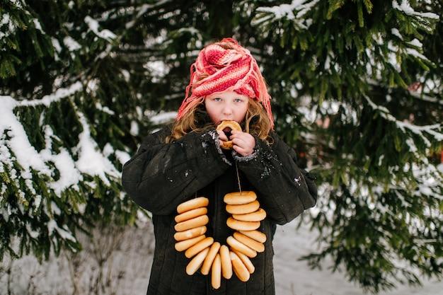 Маленькая смешная девочка во взрослой негабаритной одежде, едящей бублик на снегу в зимний день. празднование традиционного праздника российской страны Premium Фотографии
