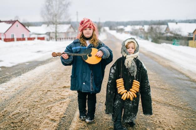 屋外の面白い子供たち。村の若者。ロシア風の伝統的な服。二人の少女が奇妙な珍しい奇妙な肖像画。大人用の特大の服を着ている子供。 Premium写真