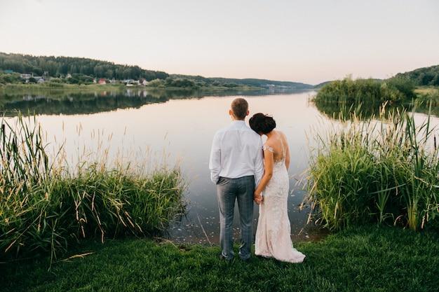 Романтический портрет сзади свадьбы пара вместе стоя на берегу на закате и наслаждаясь видом на озеро. Premium Фотографии