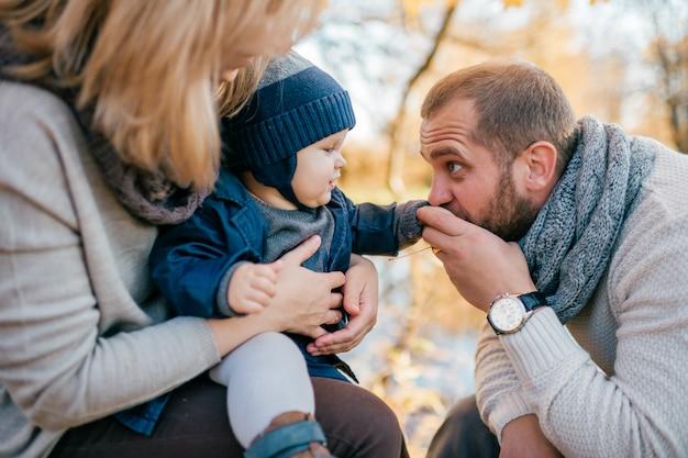 晴れた日に秋の公園で小さな子供と幸せな家族カップル Premium写真