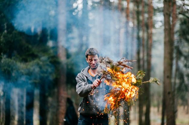 Счастливый человек с грязным лицом и эмоциональным выражением держит горящие ветви в руках в лесу. Premium Фотографии