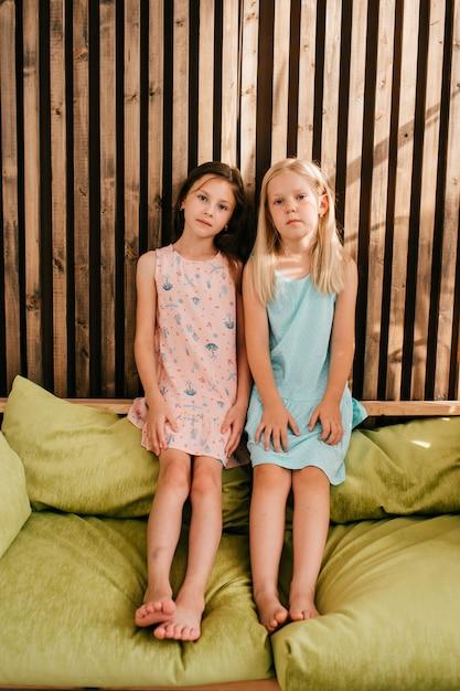 Две маленькие девочки в красивых платьях сидят на лимонной кровати с деревянной стеной позади них Premium Фотографии