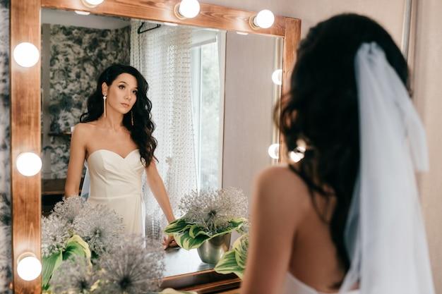 Красивая невеста в свадебном платье, глядя в зеркало Premium Фотографии