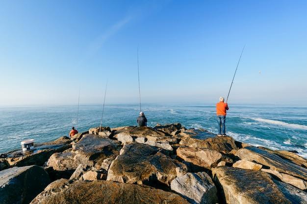 海で釣りをする男性のグループ Premium写真