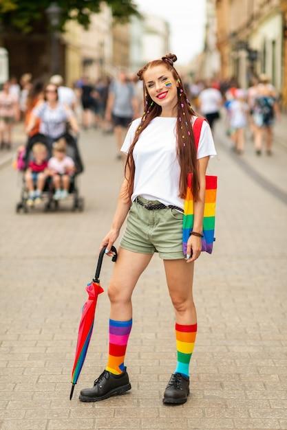 Образ жизни портрет красочной девушки с флагом лгбт на лице, позирует на улице Premium Фотографии