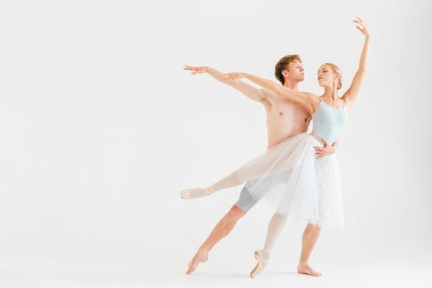 ホワイトスタジオの背景にポーズをとって現代のバレエダンサーの若いカップル Premium写真