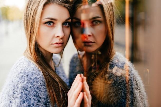 ミラーウィンドウで驚くほど若い女の子の自己反射の肖像画。自我の概念を変える。 Premium写真
