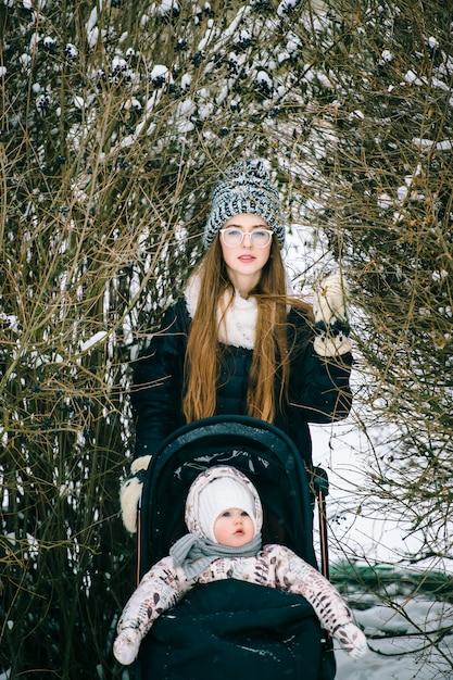 Стильная молодая мать, прогулки с дочерью в коляске в снежном зимнем парке. Premium Фотографии