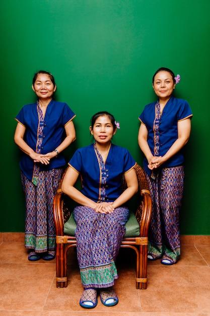緑の背景に伝統的な服の肖像画でタイの女性マッサージ師。 Premium写真