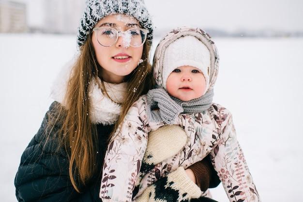 冬の雪原で彼女の素敵な赤ちゃんと遊んで幸せな若い母。 Premium写真