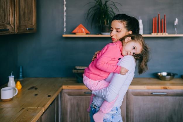 キッチンで彼女の小さな面白い娘と遊ぶ愛らしい若い女性。ハグ、携帯、彼女の小さな女性の子供を見ているかなりの母の肖像画。 Premium写真