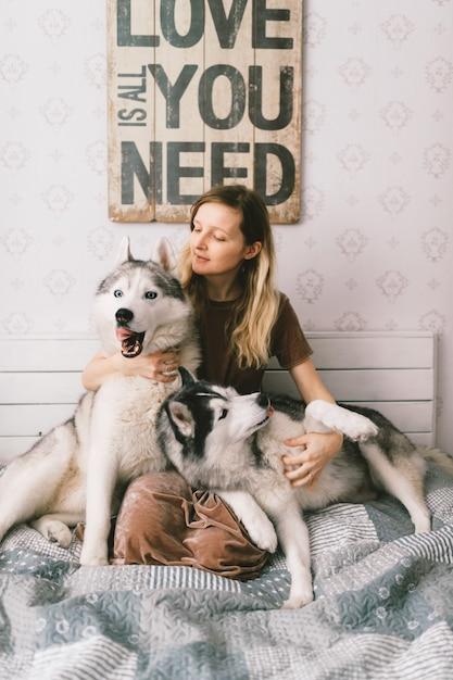 Молодая счастливая женщина в коричневом платье сидя на кровати и обнимая прелестных осиплых щенят. Premium Фотографии