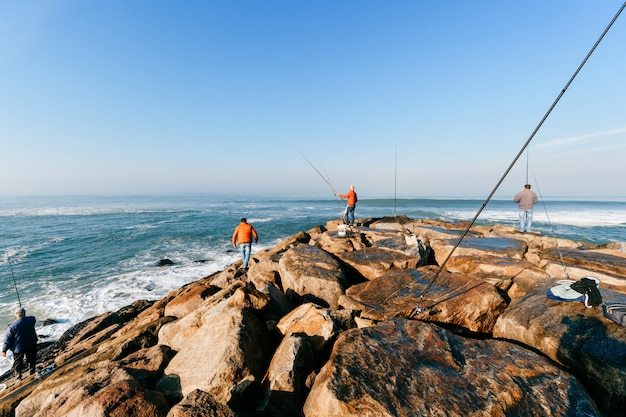 海で釣りをしている認識できない成人男性のグループ Premium写真