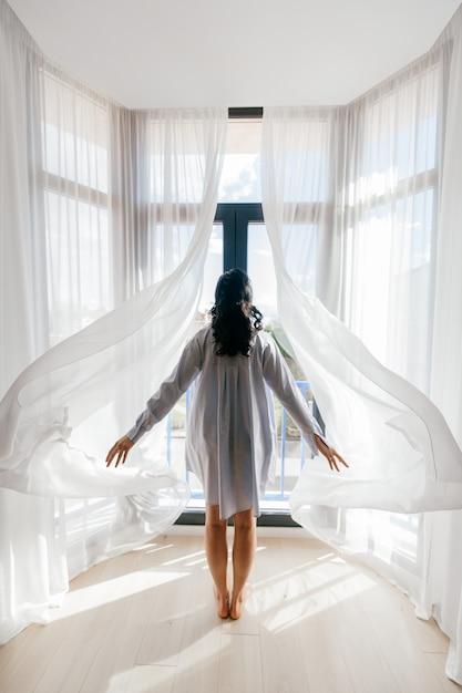 Молодая девушка стоит спиной и открывает шторы. Premium Фотографии