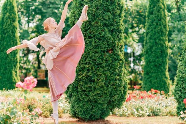 エレガントなバレリーナは、美しいイタリアの庭でバレエのポーズを示しています Premium写真