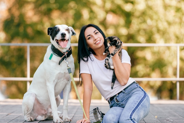 小さな猫と公園で屋外に座っている大きなハウンド犬と美しい若いブルネットの少女のライフスタイルの肖像画。素敵なペットを抱いて幸せな笑みを浮かべて十代。飼い主とかわいい動物の友情 Premium写真