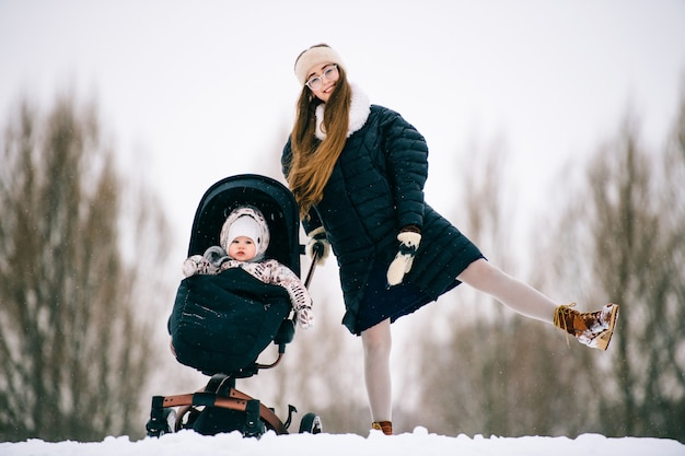 スタイリッシュな美しい若い母親は、冬に屋外のベビーカーに座っている素敵な子供と一緒に楽しんでいます。幸せな陽気な女性と雪で遊ぶ幼児の娘。 Premium写真