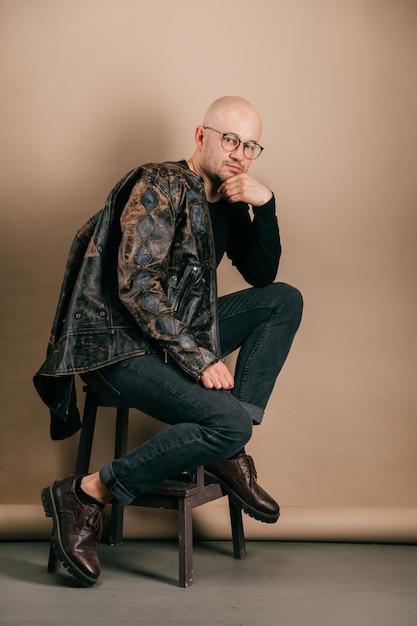スタジオでコーヒー紙の背景にポーズのスタイリッシュな服で大人のハゲ自信を持って男の肖像。 Premium写真