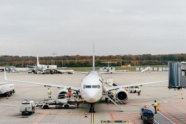 ケルンボン空港の従業員は、着陸した飛行機にサービスを提供しています。待合室から滑走路の窓を通して眺める Premium写真