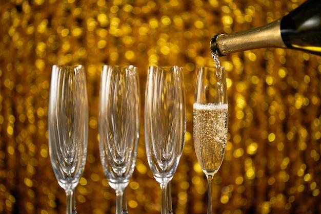 Розлив шампанского в бокал по золотому стильному цвету Premium Фотографии