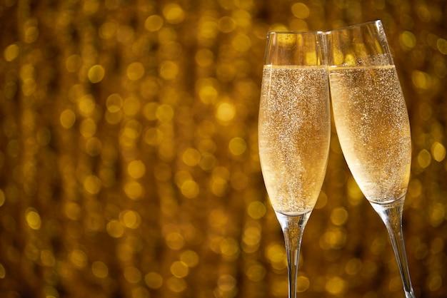 Два бокала шампанского на блестящие эффекты боке Premium Фотографии