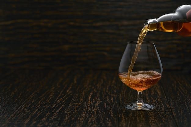 Лить коньяк из бутылки в стакан с деревянной стеной. Premium Фотографии