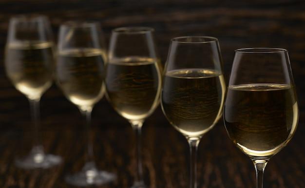 Белое вино на черном деревянном столе, конец вверх. Premium Фотографии