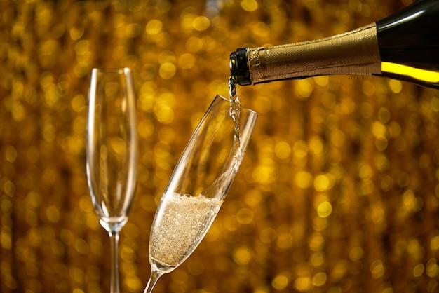 テキストの黄金ボケ円の場所でスタイリッシュな黄金のグラスにシャンパンを注ぐ Premium写真