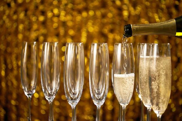 Наливая шампанское в бокал на свету, Premium Фотографии