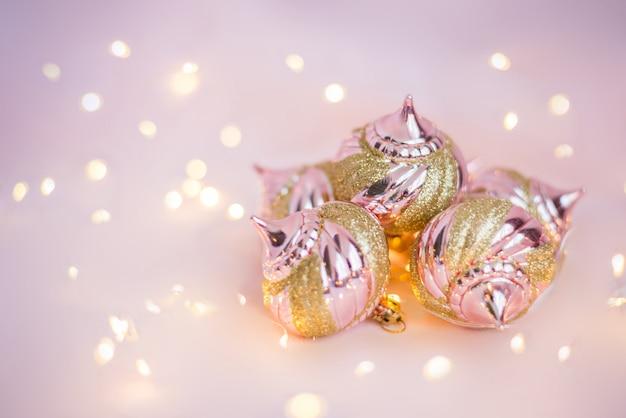 ライトと明るいピンクの表面にクリスマスのおもちゃ Premium写真