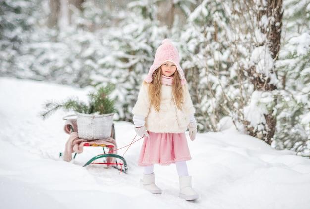 冬の森でかわいい女の子がそりで歩く Premium写真