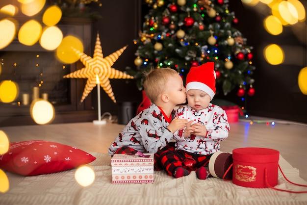 Мальчики, братья, дети в новогодних костюмах, пижамы с елочными украшениями Premium Фотографии