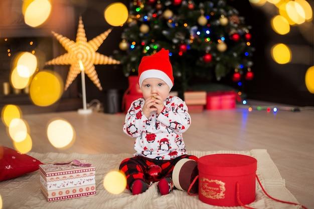 Счастливый мальчик, малыш в красной шапке санта сидит с елочными украшениями Premium Фотографии