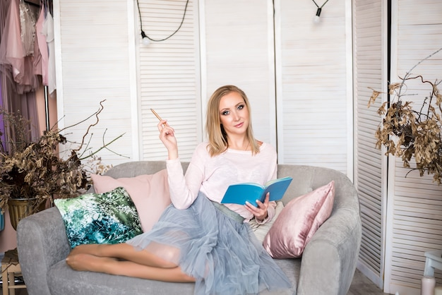 モダンな光の家で計画して、メモ帳とペンで座っている女性ブロンドの髪灰色のソファ。 Premium写真