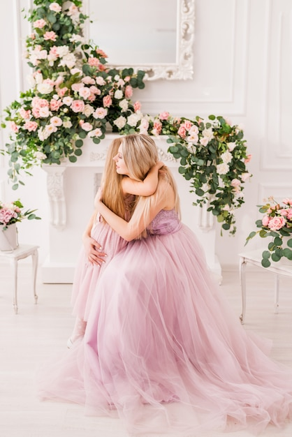 花の美しいインテリアでエレガントなドレスで母と娘の肖像画。 Premium写真