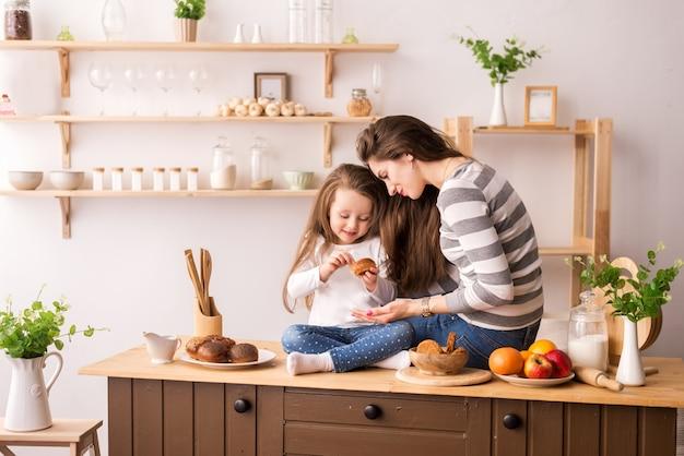 朝食を準備するキッチンで陽気な母と娘。彼らはクッキーを食べ、パンケーキをし、笑います。 Premium写真