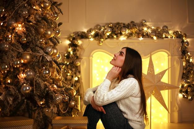 Мечтательная женщина возле елки с огнями украшения и подарки Premium Фотографии